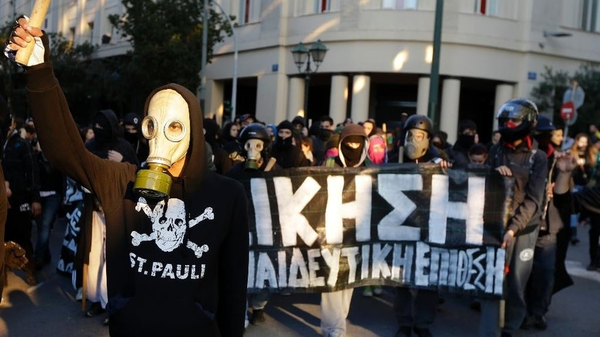 Masked youths take part as they hold a banner reading ''Revenge'' during a protest in central Athens, on Saturday, Dec. 6, 2014. Thousands of protesters gathered to mark the sixth anniversary of the fatal police shooting of an unarmed teenager in the Greek capital that led to widespread rioting. This year's anniversary marches come as nearly nightly violent protests by supporters of one of Grigoropoulos' friends, jailed anarchist and convicted bank robber Nikos Romanos. He is on hunger strike demanding prison leave to attend lectures after he passed university entrance exams. (AP Photo/Thanassis Stavrakis)