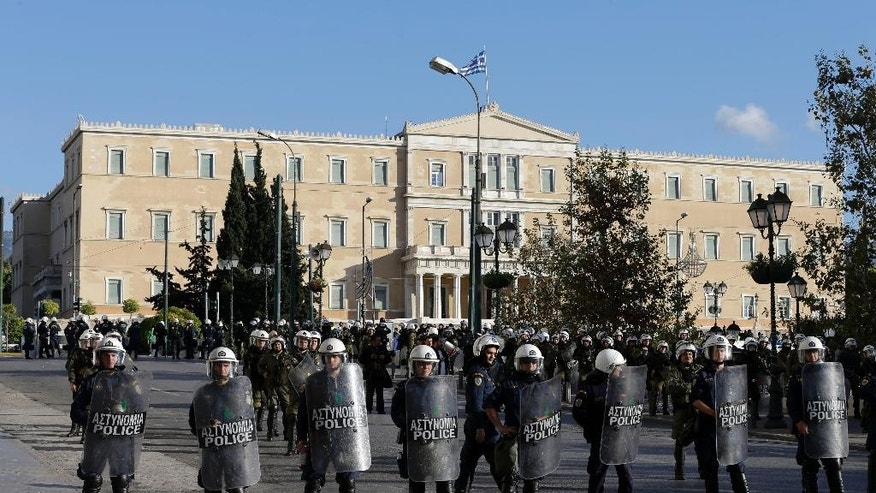 Riot police block the road outside luxury hotels as the Greek parliament is seen in the background during a rally in central Athens, on Saturday, Dec. 6, 2014. Thousands of protesters gathered to mark the sixth anniversary of the fatal police shooting of an unarmed teenager in the Greek capital that led to widespread rioting. This year's anniversary marches come as nearly nightly violent protests by supporters of one of Grigoropoulos' friends, jailed anarchist and convicted bank robber Nikos Romanos. He is on hunger strike demanding prison leave to attend lectures after he passed university entrance exams. (AP Photo/Thanassis Stavrakis)