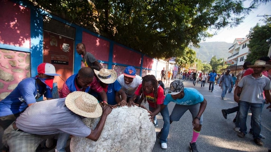 Anti-government demonstrators move a large stone to the middle of the street as they call for the resignation of Haiti's President Michel Martelly in Port-au-Prince, Haiti, Saturday, Dec. 6, 2014. (AP Photo/Dieu Nalio Chery)