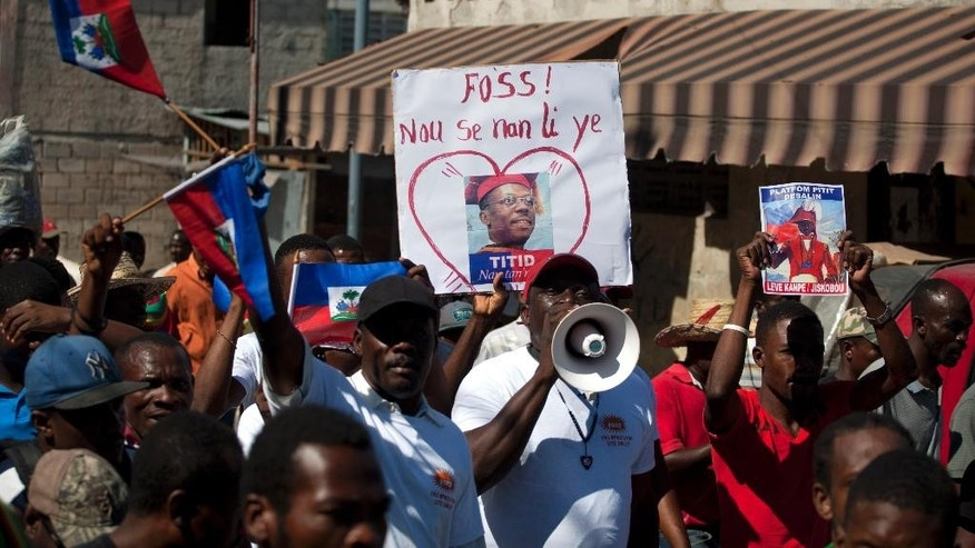 "An anti-government protester holds up an image of Haiti's former President Jean Bertrand Aristide that reads in Creole ""Our strength is in Aristide"" during a demonstration calling for the resignation of Haiti's President Michel Martelly in Port-au-Prince, Haiti, Saturday, Dec. 6, 2014. Protesters marched for the second time in two days amid anger over delayed elections and other issues. (AP Photo/Dieu Nalio Chery)"