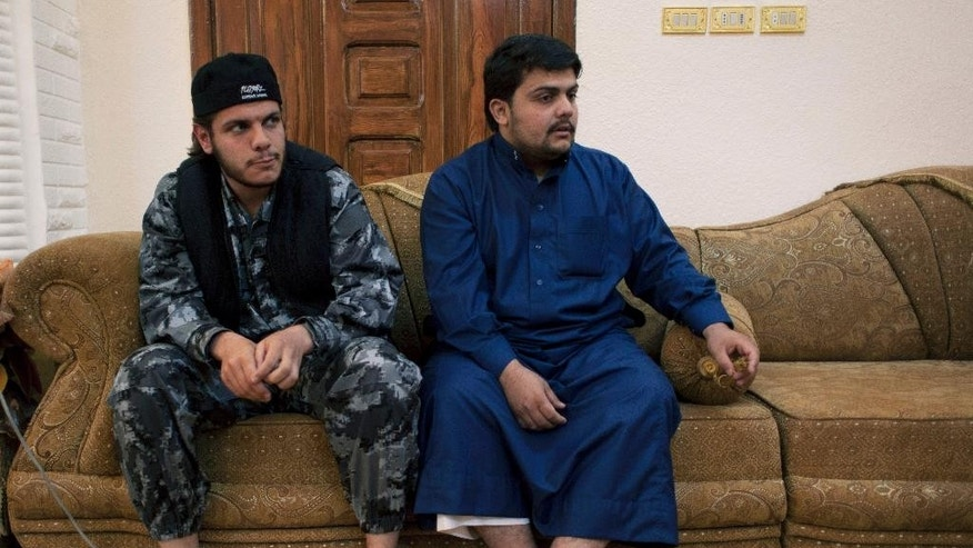 In this photo taken Oct. 28, 2014, Omar Mansour, 23, right, who briefly joined jihadists in Syria, and his brother Abdullah, 21, who was recruited to join al-Qaida in Yemen, sit at the family house during an interview with the Associated Press, in the city of Ma'an, Jordan. Now they are home, trying to live ordinary lives, but believe their hardline vision of Islam is gaining popularity. (AP Photo/Nasser Nasser)