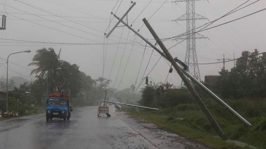 Dec. 7, 2014: Motorists pass by toppled electrical posts due to strong winds brought by Typhoon Hagupit in Camalig, Albay province, eastern Philippines. (AP)