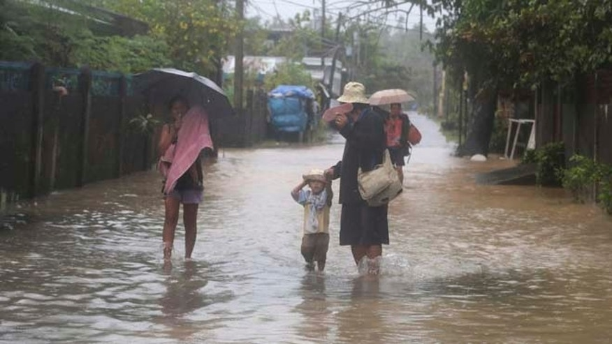 Dec. 7, 2014: A family walks along a flooded street during a heavy rain brought by Typhoon Hagupit in Legazpi, Albay province, eastern Philippines. (AP)
