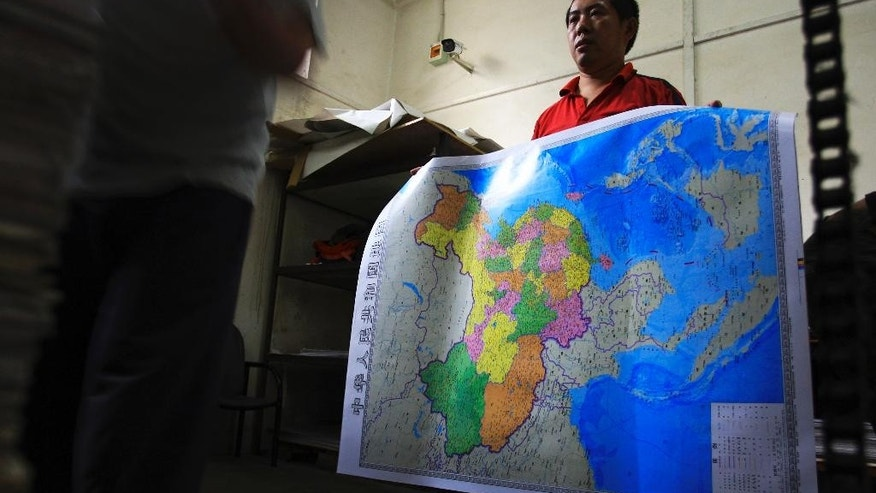 In this June 27, 2014 photo, a worker holds a new officially approved map of China that includes the islands and maritime area that Beijing claims in the South China Sea, at a printing factory in Changsha in south China's Hunan province.  China has again rejected an attempt by the Philippines to challenge its territorial claims over the South China Sea through international arbitration, releasing a lengthy paper a week before the Dec. 15, 2014 deadline for China to respond to the case. China prefers to settle its disputes with discussions with the countries directly involved. But the Philippines has filed a case with an international tribunal. (AP Photo) CHINA OUT