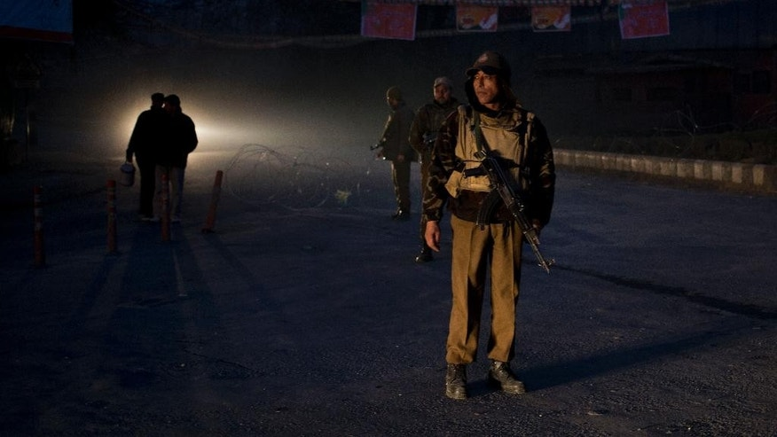 Indian policemen stand guard as they close a road to traffic in Srinagar, Indian controlled Kashmir, Sunday, Dec. 7, 2014. Thousands of government forces have fanned out across the Indian portion of Kashmir to provide a security shield for Prime Minister Narendra Modi, who is scheduled to make a campaign speech Monday ahead of local elections. (AP Photo/Dar Yasin)