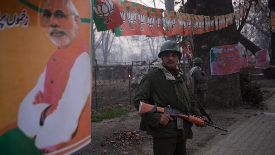 Indian paramilitary soldiers stand guard outside Sheri Kashmir cricket stadium where Prime Minister Narendra Modi, photograph on left, is expected to make campaign speech Monday ahead of local elections in Srinagar, India, Sunday, Dec. 7, 2014. Thousands of government forces have fanned out across the Indian portion of Kashmir to provide a security shield for Modi. (AP Photo/Dar Yasin)