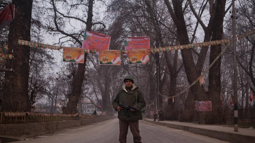 An Indian paramilitary soldier stands guard near Sheri Kashmir cricket stadium where Prime Minister Narendra Modi, photographs above, is expected to make campaign speech Monday ahead of local elections in Srinagar, India, Sunday, Dec. 7, 2014. Thousands of government forces have fanned out across the Indian portion of Kashmir to provide a security shield for Modi. (AP Photo/Dar Yasin)