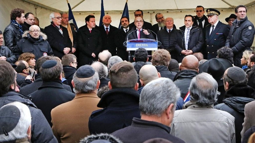 French interior minister Bernard Cazeneuve, center, during a gathering against anti-semitism also attended by Israeli ambassador to France Yossi Gal, left, in Creteil, east of Paris, Sunday Dec. 7, 2014. An attack on a French Jewish couple this week, had revived worries about long-simmering anti-Semitic sentiment in France. The number of anti-Semitic incidents in France has grown 91 percent this year compared to last year, said Roger Cukierman, head of France's leading Jewish organization, CRIF. (AP Photo/Remy de la Mauviniere)