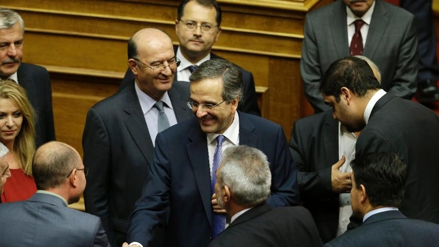 "Greece's Prime Minister Antonis Samaras, center, is congratulated by his government's lawmakers after a parliament meeting for a vote on the country's 2015 budget in Athens early Monday, Dec. 8, 2014. Greece's 300-member Parliament passed the 2015 budget early Monday, with 155 members voting for and 134 against. One deputy voted ""present"".  (AP Photo/Thanassis Stavrakis)"