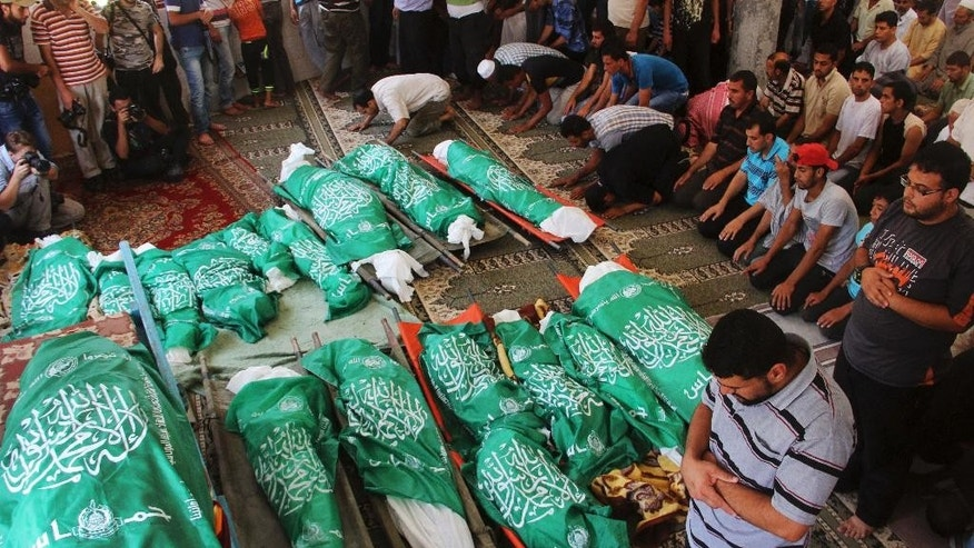 FILE - In this Monday, July 21, 2014, file photo, Palestinians pray over the Hamas flag-draped bodies of members of the Abu Jamea family during their funeral at the main mosque in Khan Younis, in the southern Gaza Strip. At least 24 members of the Abu Jamea family were killed in the July 20 strike on their home. Among those killed were 18 children between the ages of six months and nine years, according to death certificates obtained by The Associated Press. The Israeli military says it has opened a criminal investigation into one of the deadliest airstrikes of the last Gaza war.  (AP Photo/Hatem Ali, File)