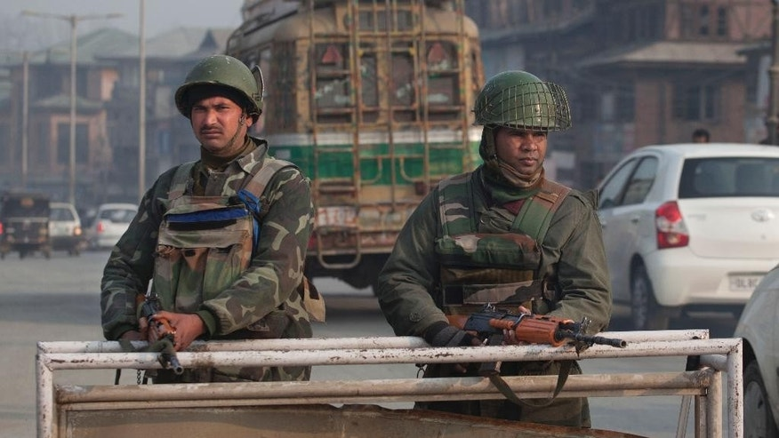 Indian paramilitary soldiers stand guard at a temporary checkpoint in Srinagar, Indian controlled Kashmir, Saturday, Dec. 6, 2014. Security was beefed up the day after militants in the disputed territory of Kashmir attacked an Indian army camp, triggering a fierce gunbattle that left 11 Indian soldiers and six suspected assailants dead, officials said. (AP Photo/Dar Yasin)