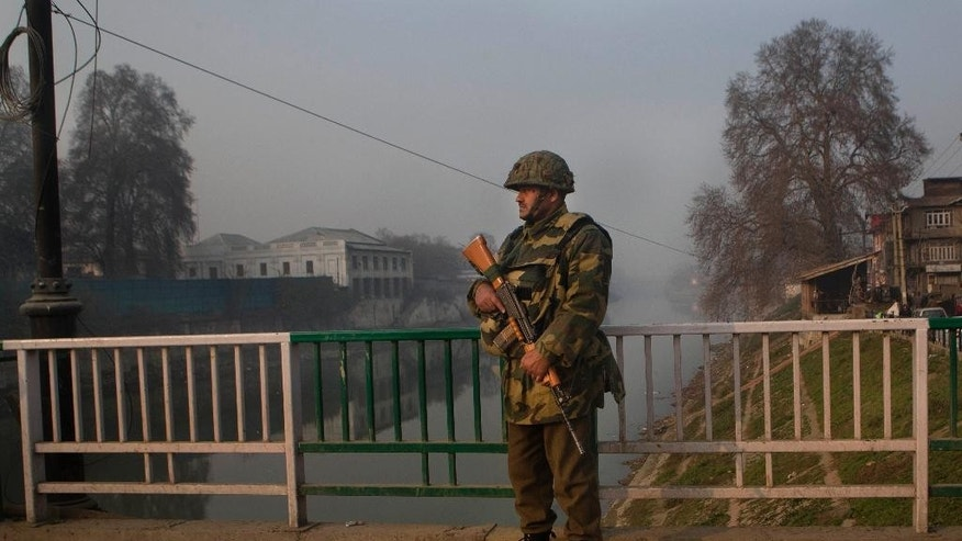 An Indian paramilitary soldier stands guard at a temporary checkpoint in Srinagar, Indian controlled Kashmir, Saturday, Dec. 6, 2014. Security was beefed up the day after militants in the disputed territory of Kashmir attacked an Indian army camp, triggering a fierce gunbattle that left 11 Indian soldiers and six suspected assailants dead, officials said. (AP Photo/Dar Yasin)