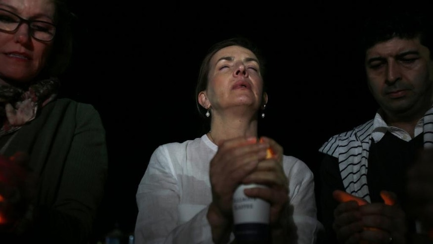 Expatriates take part in a candlelight vigil, in memory of American schoolteacher Ibolya Ryan, who was killed in a stabbing attack in the restroom of the Boutik Mall on the upscale Reem Island in Abu Dhabi, on Dec. 1, 2014, at a beach in Dubai, United Arab Emirates, Sunday, Dec. 7, 2014. (AP Photo/Kamran Jebreili)