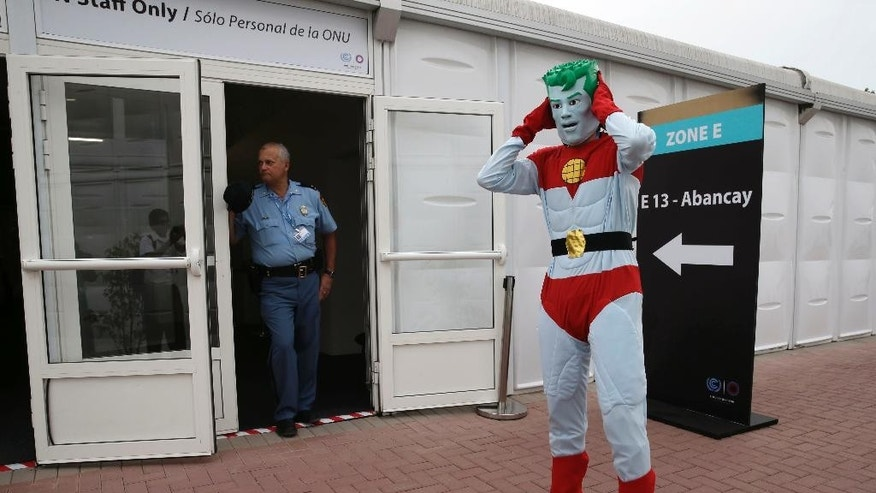 A man dressed as the superhero Captain Planet stands outside a conference room used by the Climate Change Conference in Lima, Peru, Thursday, Dec. 4, 2014. A recent study by a top Brazilian climate scientist, Antonio Nobre, draws together data from multiple researchers to show that the Amazon, due to decades of deforestation, may be closer to a tipping point than the government has acknowledged and that the changes could be a threat to climates around the globe. (AP Photo/Martin Mejia)