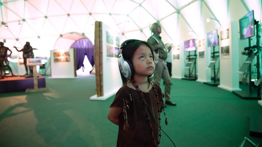 An Ashaninka indigenous youth watches an educational video inside the Indigenous Pavilion at the Climate Change Conference in Lima, Peru, Thursday, Dec. 4, 2014. Delegates from more than 190 countries are meeting in Lima for the next two weeks to work on drafts for a global climate deal that is supposed to be adopted next year in Paris. (AP Photo/Martin Mejia)