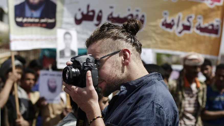 "In this Tuesday, April 16, 2013 photo, Luke Somers, 33, an American photojournalist who was kidnapped over a year ago by al-Qaida, uses a camera during a demonstration demanding the release of Yemeni detainees in Guantanamo Bay prison in front of the U.S. embassy in Sanaa, Yemen. Somers and a South African teacher held by al-Qaida militants in Yemen were killed Saturday, Dec. 6, 2014 during a U.S.-led rescue attempt, a raid President Barack Obama said he ordered over an ""imminent danger"" to the reporter. (AP Photo/Hani Mohammed)"