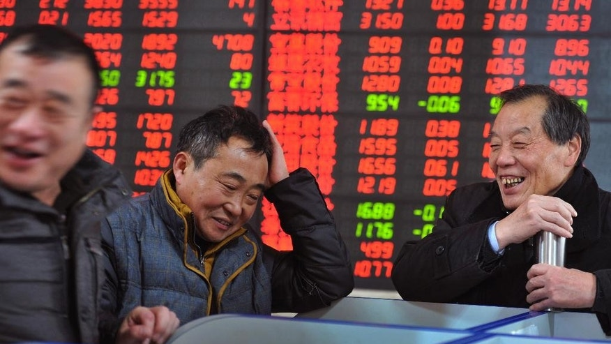 In this Dec. 4, 2014 photo, investor share a light moment as they check on stock prices at a brokerage house in Fuyang in central China's Anhui province. Economic growth fell to a five-year low of 7.3 percent in the latest quarter but investor sentiment was recharged by Beijing's surprise interest rate cut Nov. 22 that is expected to put a floor under the slump. (AP Photo) CHINA OUT