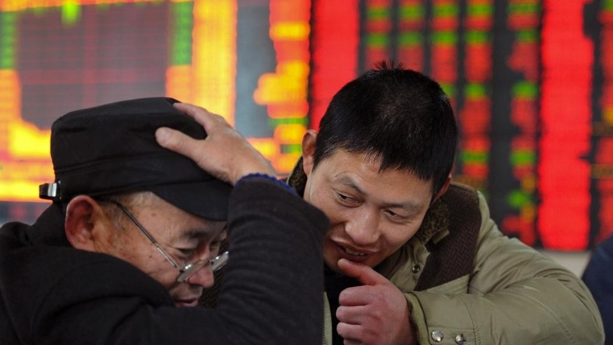 In this Dec. 4, 2014 photo, investor check on stock prices at a brokerage house in Fuyang in central China's Anhui province. Buoyed by hopes for an economic rebound combined with outright cheerleading by the state press, the market benchmark has soared 47 percent since June, including 8 percent last week alone. (AP Photo) CHINA OUT
