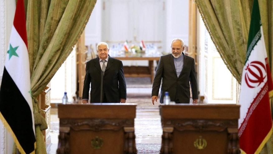 "Iranian Foreign Minister Mohammad Javad Zarif, right, and his Syrian counterpart Walid al-Moallem arrive to attend a joint press conference in Tehran, Iran, Monday, Dec. 8, 2014. Russia on Monday demanded an explanation for Israeli airstrikes on two areas near Damascus, while the Syrian and Iranian foreign ministers called it an act of aggression that proves Israel was ""in the same trench"" with extremist groups fighting the Syrian government. (AP Photo/Ebrahim Noroozi)"