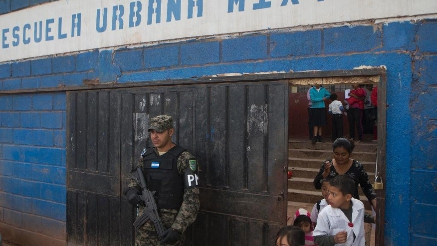 In this photo Nov. 28, 2014 photo, a member of Hondura's Military Police, stands guard at the entrance of a school, during the last day of class, in the Canaan neighborhood of Tegucigalpa, Honduras. Street gangs control most schools in Tegucigalpa, where a lot of the students are gangsters, along with their parents. (AP Photo/Esteban Felix)
