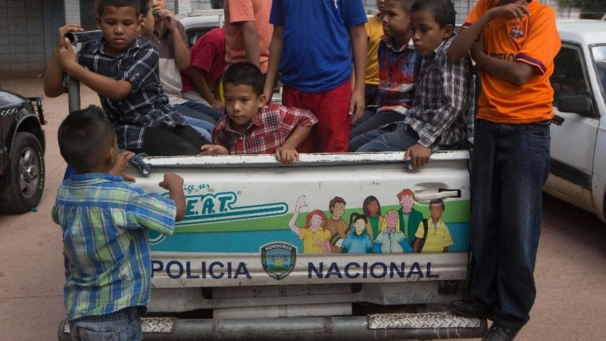 "In this Nov. 26, 2014 photo, a group of children climb into the back of a pick-up truck belonging to the National Police, play at being arrested mimicking detained gang members, in front of a school in Tegucigalpa, Honduras. Accordig to Yojana Corrales, a police officer with the capital's gang prevention unit,  ""This is the image of the gang leader,"" she said. ""The detainee is a somebody in the barrio, and those kids want to be a somebody."" (AP Photo/Esteban Felix)"