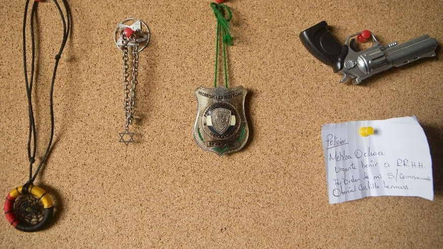 "In this Nov, 26, 2014 photo, items seized from school children hang on a wall at a Prevention and Assistance Program Anti-Gang of the Honduran National Police delegation in Tegucigalpa, Honduras. The dream catcher and star of David were used by Mara gang members to ""mark"" their young recruits, using symbols that won't alert suspicion. Street gangs control most schools, where a lot of the students are gangsters, along with their parents. (AP Photo/Esteban Felix)"