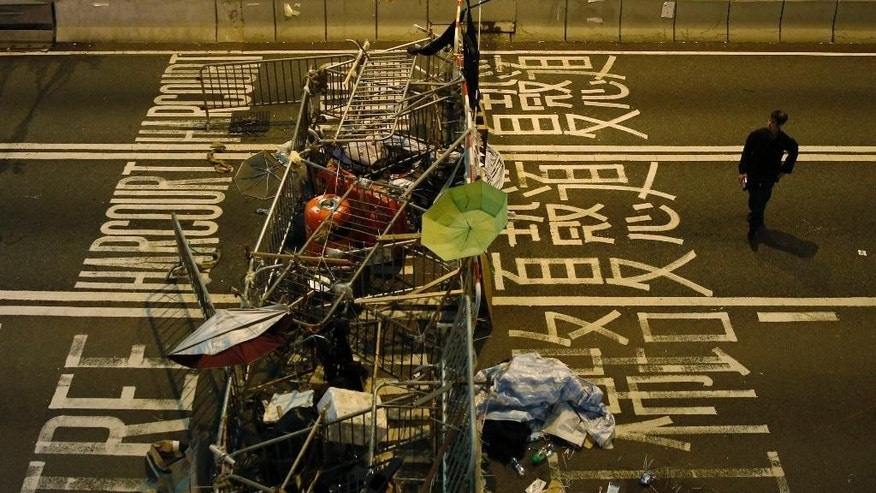 A man walks past a barricade which was set up by pro-democracy protesters at the occupied area outside government headquarters in Hong Kong  Monday, Dec. 8, 2014. Leaders the Hong Kong Federation of Students, representing those studying at colleges, said last Thursday that they were considering a retreat from the protest sites and expect to come to a decision soon. (AP Photo/Kin Cheung)