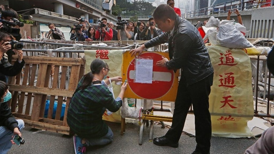 Members of bailiff post an injunction document on a barricade set up by pro-democracy protesters at the occupied area outside government headquarters in Hong Kong Tuesday, Dec. 9, 2014. Hong Kong authorities and activists are set for one last showdown after the publication Tuesday of a court order authorizing the removal of barricades and tents blocking the Asian financial hub's streets for more than two months. (AP Photo/Kin Cheung)
