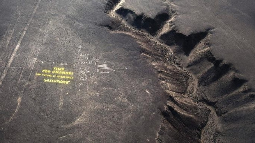 """Greenpeace activists stand next  to massive letters delivering the message """"Time for Change: The Future is Renewable"""" next to the hummingbird geoglyph in Nazca in Peru, Monday, Dec. 8, 2014. Greenpeace activists from Brazil, Argentina, Chile, Spain, Germany, Italy and Austria displayed the message, which can be viewed from the sky, during the climate talks in Peru, to honor the Nazca people, whose ancient geoglyphs are one of the country's cultural landmarks. (AP Photo/Rodrigo Abd)"""