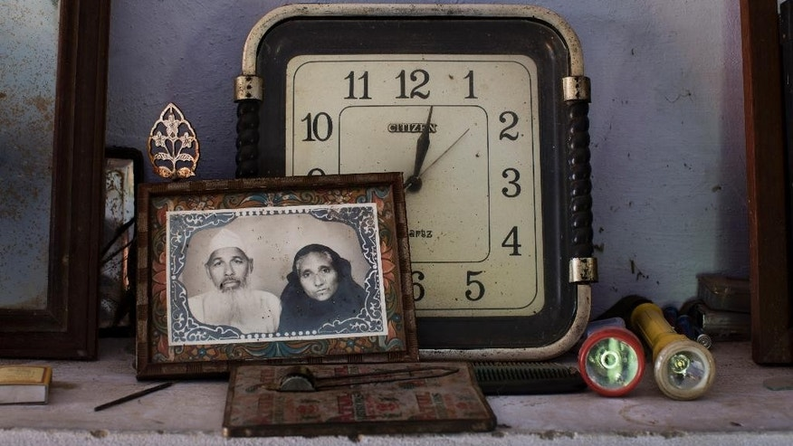 In this Nov. 27, 2014 photo, a portrait of retired postman Faizul Hasan Qadri and his late wife Tajammuli is placed on a shelf inside Faizul's house in the town of Kaser Kalan, in the Indian state of Uttar Pradesh. After she died, he sold her small pieces of jewelry and some family farmland, added everything he'd saved over the years and started building a mausoleum in her memory as a proof of love. (AP Photo/Bernat Armangue)
