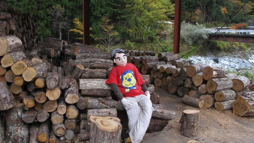 In this Thursday, Nov. 6, 2014 photo, a teenager look alike scarecrow sits on a log pile in Nagoro, Tokushima Prefecture, southern Japan. This village deep in the rugged mountains of southern Japan once was home to hundreds of families. Now, only 35 people remain, outnumbered three-to-one by scarecrows that Tsukimi Ayano crafted to help fill the days and replace neighbors who died or moved away. (AP Photo/Elaine Kurtenbach)