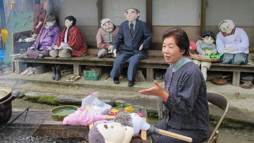 "In this Thursday, Nov. 6, 2014 photo, Tsukimi Ayano speaks as she stitches a scarecrow girl by her outdoor hearth at her home in the mountainous village of Nagoro, Tokushima Prefecture, southern Japan. This village deep in the rugged mountains of southern Japan once was home to hundreds of families. Now, only 35 people remain, outnumbered three-to-one by scarecrows that Ayano crafted to help fill the days and replace neighbors who died or moved away. At 65, Ayano is one of the younger residents of Nagoro. She moved back from Osaka to look after her 85-year-old father after decades away. ""They bring back memories,"" Ayano said of the life-sized dolls crowded into corners of her farmhouse home. (AP Photo/Elaine Kurtenbach)"
