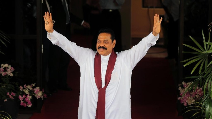 Sri Lankan President Mahinda Rajapaksa waves to supporters as he arrives to hand over nomination papers in Colombo, Sri Lanka, Monday, Dec. 8, 2014. Rajapaksa and his former health minister Maithripala Sirisena were among 19 people Monday to hand in nominations to contest the island's presidential election next month. (AP Photo/Eranga Jayawardena)