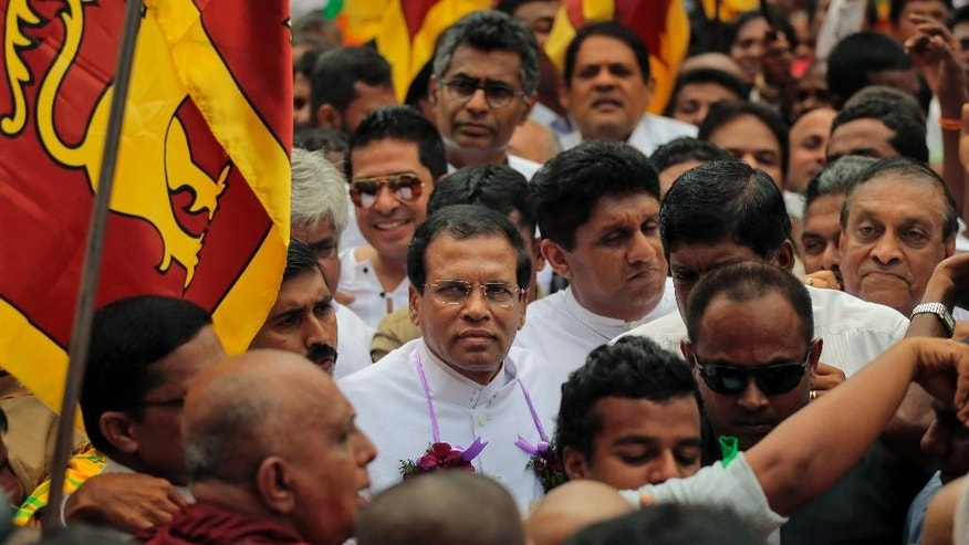 Sri Lankan presidential candidate of the common opposition Maithripala Sirisena, center wearing spectacles, is surrounded by his supporters as he leaves after filing his nomination papers, in Colombo, Sri Lanka, Monday, Dec. 8, 2014. Sri Lankan President Mahinda Rajapaksa and his former health minister Sirisena were among 19 people Monday to hand in nominations to contest the island's presidential election next month. (AP Photo/Eranga Jayawardena)