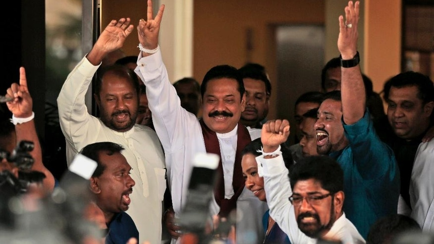 Sri Lankan President Mahinda Rajapaksa displays the victory sign after filing his nomination in Colombo, Sri Lanka, Monday, Dec. 8, 2014. Rajapaksa and his former health minister Maithripala Sirisena were among 19 people Monday to hand in nominations to contest the island's presidential election next month. (AP Photo/Eranga Jayawardena)