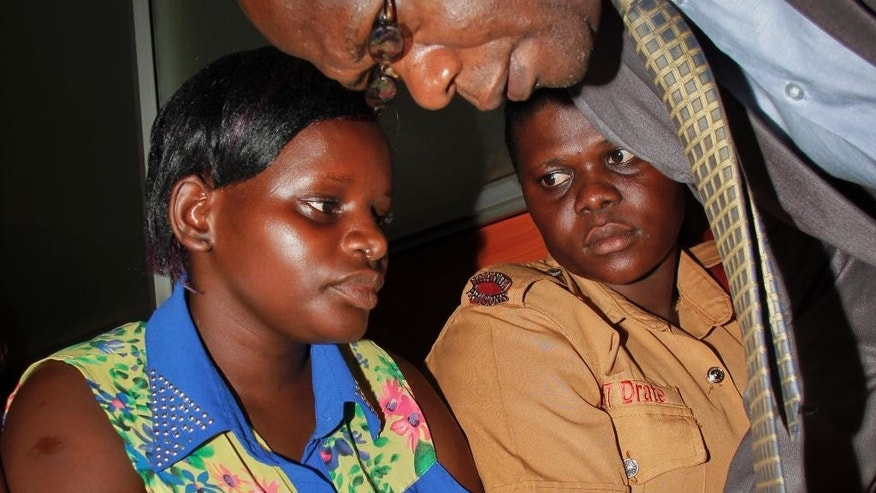 Ugandan maid Jolly Tumuhiirwe, left, speaks with her lawyer Ladislaus Rwakafuuzi, above, as a prison officer sits next to her at a court in Kampala, Uganda Monday, Dec. 8, 2014. Tumuhiirwe has pleaded guilty to charges of torturing a child who was under her care in a case that shocked Ugandans and sparked debate about the role of maids raising children, however her lawyer said she had not received a fair trial and did not understand the charges. (AP Photo)