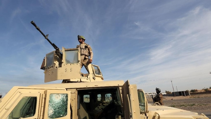 Iraqi security forces are deployed during a military operation to regain control of the villages around the town of Tikrit, 80 miles (130 kilometers) north of Baghdad, Iraq, Monday, Dec. 8, 2014.  The commander of U.S. forces fighting the Islamic State in Iraq and Syria, Army Lt. Gen. James Terry says the extremist group has been thrown on the defensive, because coalition airstrikes and other measures are taking a toll on IS ability to communicate. (AP Photo/Hadi Mizban)