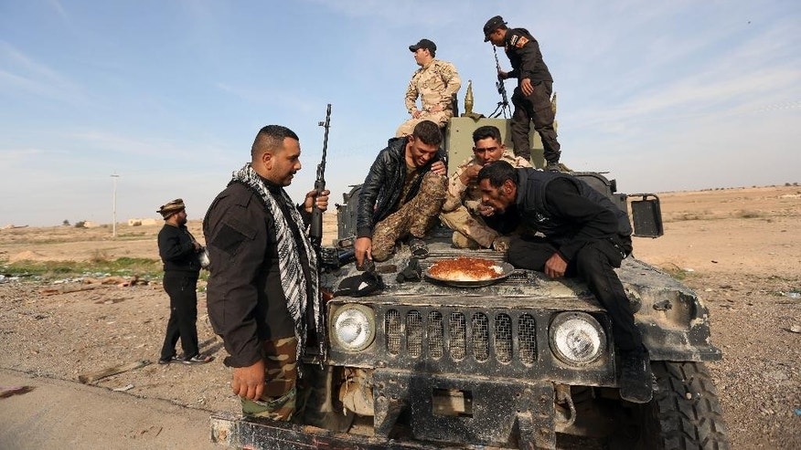 Iraqi security forces and Shiite fighters eat the lunch food after a military operation to regain control of villages around the town of Beiji, some 250 kilometers (155 miles) north of Baghdad, Iraq, Monday, Dec. 8, 2014.  The commander of U.S. forces fighting the Islamic State in Iraq and Syria, Army Lt. Gen. James Terry says the extremist group has been thrown on the defensive, because coalition airstrikes and other measures are taking a toll on IS ability to communicate. (AP Photo/Hadi Mizban)