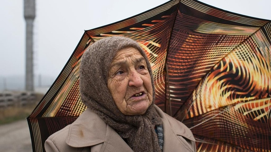 In this photo taken on Friday, Oct.  24, 2014, Rebiya Setarova, 80, wrapped in a woolen shawl,  speaks to the Associated Press at a dirt road ahead of Friday's prayer in Sary-Su, Crimea. Since Russia annexed Crimea from Ukraine, armed men have shown up frequently and at odd hours to search the cinder-block houses, mosque and school in this settlement of Tatars, a Muslim ethnic minority that has suffered a history of discrimination in the peninsula that is its historic homeland. (AP Photo/Alexander Zemlianichenko)