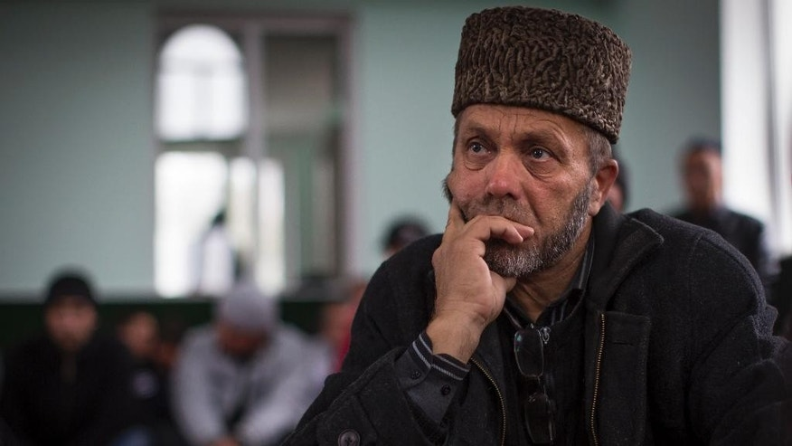 In this photo taken on Friday, Oct.  24, 2014, Abdureshit Dzhapparov, whose son was kidnapped on the streets of Sary-Su in September 2014 waits for a Friday's prayer at a mosque in Sary-Su, Crimea   Since Russia annexed Crimea from Ukraine, armed men have shown up frequently and at odd hours to search the cinder-block houses, mosque and school in this settlement of Tatars, a Muslim ethnic minority that has suffered a history of discrimination in the peninsula that is its historic homeland.  (AP Photo/Alexander Zemlianichenko)