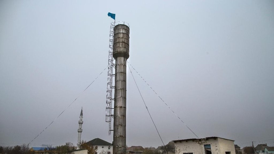 In this photo taken on Friday, Oct.  24, 2014, shows a view of the center of Sary-Su, Crimea, with a water tower, center, and a mosque, left.  Since Russia annexed Crimea from Ukraine, armed men have shown up frequently and at odd hours to search the cinder-block houses, mosque and school in this settlement of Tatars, a Muslim ethnic minority that has suffered a history of discrimination in the peninsula that is its historic homeland. (AP Photo/Alexander Zemlianichenko)