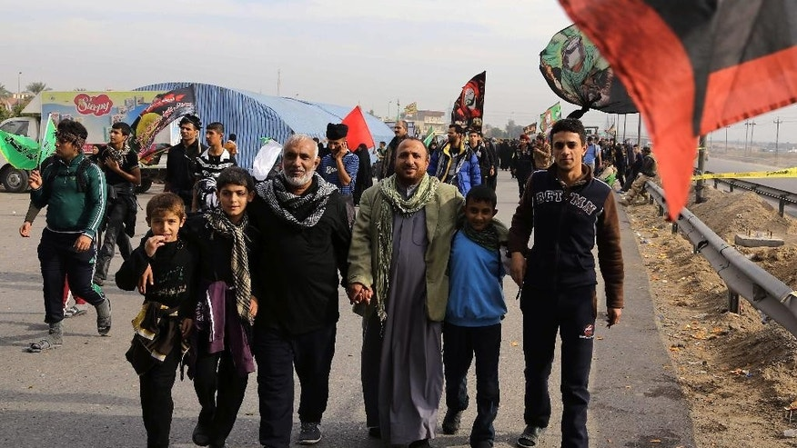 Shiite pilgrims march towards Karbala for the Arbaeen holiday in Baghdad, Iraq, Tuesday, Dec. 9, 2014. Arbaeen marks the end of a forty day mourning period following the anniversary of the 7th century martyrdom of Imam Hussein, the Prophet Muhammad's grandson. (AP Photo/Karim Kadim)