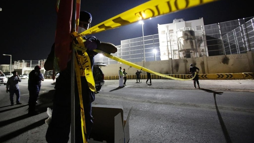 """Bahrain police cordon off and investigate the scene where a police officer was killed just outside the Molotov-scarred police station in the village of Dumistan, Bahrain, Monday, Dec. 8, 2014. Bahrain's Interior Ministry says a policeman has been killed southwest of the capital Manama, in what authorities said was a """"terror attack."""" (AP Photo/Hasan Jamali)"""