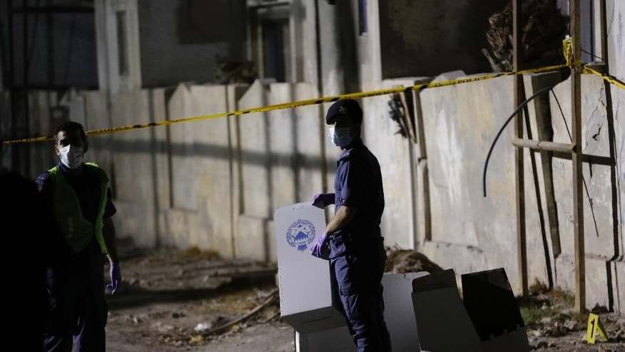 """Bahrain police collect evidence at the scene where a police officer was killed just outside the Molotov-scarred police station in the village of Dumistan, Bahrain, Monday, Dec. 8, 2014. Bahrain's Interior Ministry says a policeman has been killed southwest of the capital Manama, in what authorities said was a """"terror attack."""" (AP Photo/Hasan Jamali)"""