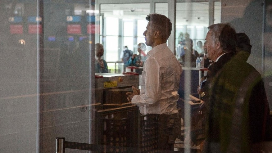 British businessman Shrien Dewani, left, prepares to leave the country at Cape Town, South Africa's airport Tuesday, Dec. 9, 2014.  On Monday Dewani had charges, relating to the murder of his newly wedded wife, Anni Dewani, thrown out of court.  (AP Photo)