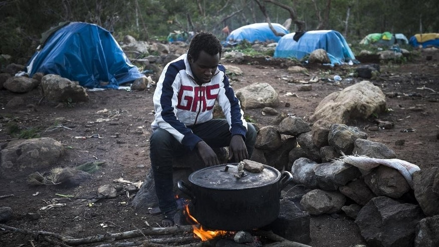 In this photo taken on Sunday, Nov. 9, 2014, a Guinean immigrant cooks dinner in a clandestine immigrants camp located at the Mount Gourougou, in the Moroccan province of Nador. After traveling thousands of miles overland from sub-Saharan Africa, destitute migrants dreaming of making it to Europe eke out an tenuous existence on the rocky slopes of Mount Gourougou, a 900-meter (2,962-foot) peak with spectacular views of their destination _ Spain's tiny North African enclave of Melilla. (AP Photo / Santi Palacios)