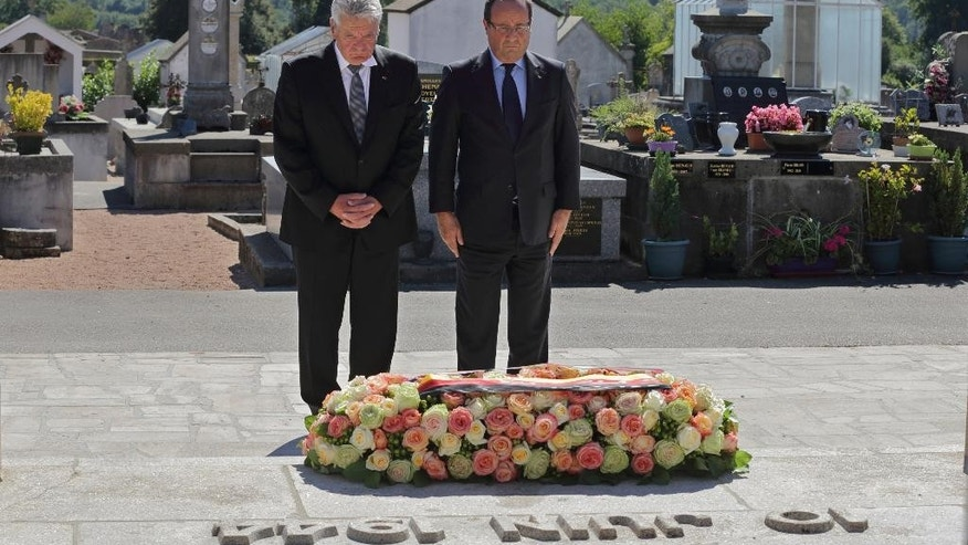 FILE - A Wednesday, Sept. 4, 2013 file photo showing France's President Francois Hollande, right, and German President Joachim Gauck, paying their respects after laying a wreath at the cemetery of the French martyr village of Oradour-sur-Glane, southwestern France. A German court on Tuesday threw out the case of a former SS man accused of involvement in the largest civilian massacre in Nazi-occupied France, saying there was not enough evidence to bring the 89-year-old to trial. Cologne resident Werner C., whose last name has not been revealed in accordance with German privacy laws, was charged with murder and accessory to murder in connection with the 1944 slaughter in Oradour-sur-Glane in southwestern France. (AP Photo/Phillipe  Wojazer, Pool, File)
