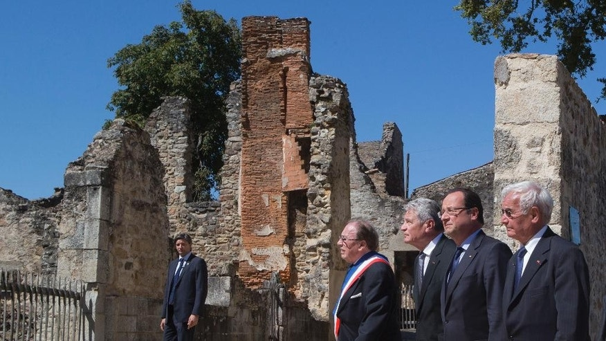 FILE - A Wednesday, Sept. 4, 2013 file photo showing from left, Mayor of Oradour-sur-Glane, Raymond Fugier, German President Joachim Gauck, French President Francois Hollande and Robert Hebras, one of the two survivors still alive, walk through the ghost city of Oradour-sur-Glane, southwestern France, where on June 10, 1944, the Nazis massacred 642 civilians. A German court on Tuesday threw out the case of a former SS man accused of involvement in the largest civilian massacre in Nazi-occupied France, saying there was not enough evidence to bring the 89-year-old to trial. Cologne resident Werner C., whose last name has not been revealed in accordance with German privacy laws, was charged with murder and accessory to murder in connection with the 1944 slaughter in Oradour-sur-Glane in southwestern France. (AP Photo/Michel Euler, Pool, File)