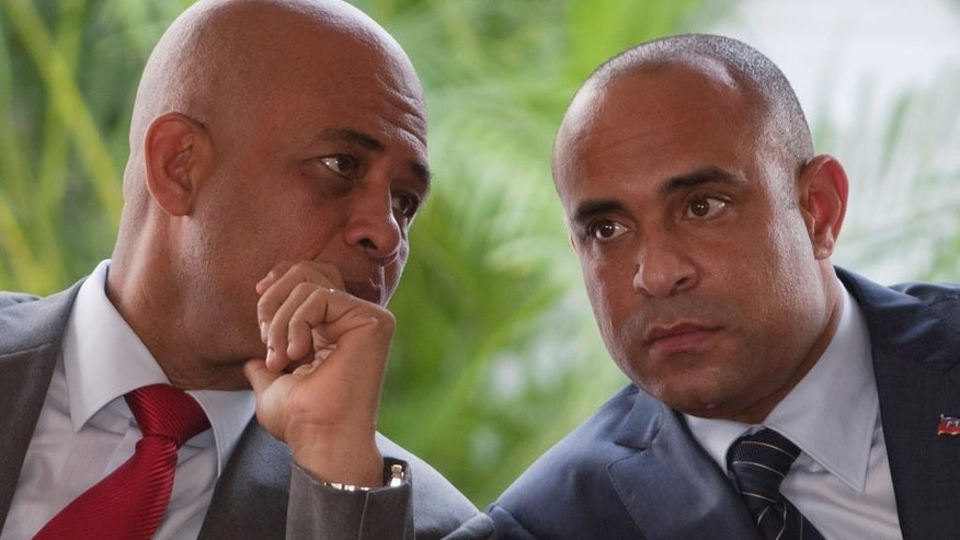 FILE - In this May 16, 2012 file photo, Haiti's President Michel Martelly, left, talks to Haiti's Prime Minister Laurent Lamothe during Lamothe's inauguration ceremony at the National Palace in Port-au-Prince, Haiti. A commission recently appointed by Martelly is calling for his prime minister to resign so a new consensus government can be formed, according to a report obtained Tuesday, Dec. 9, 2014 by The Associated Press. The panel was appointed by Martelly to help resolve a political stalemate holding up long-delayed legislative and municipal elections. (AP Photo/Dieu Nalio Chery, File)
