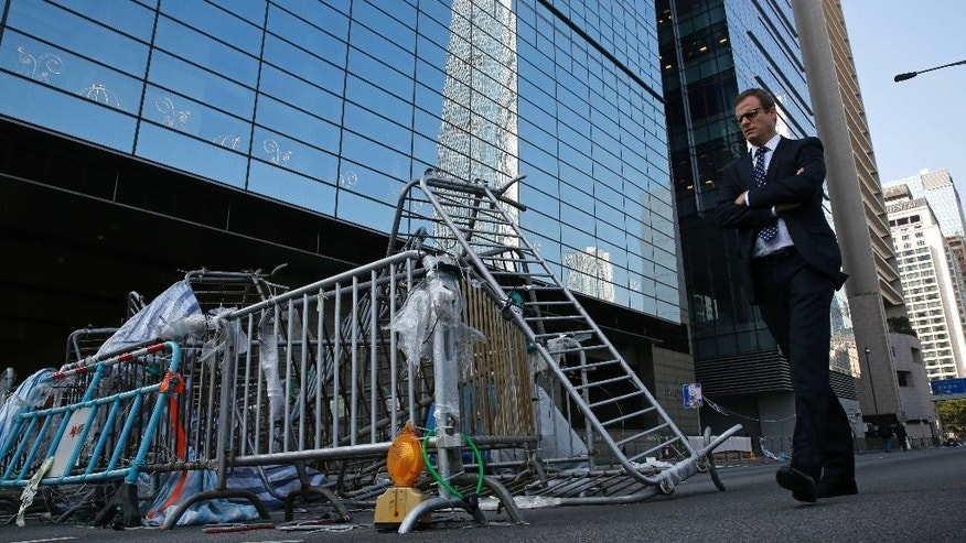 A man walks past a barricade at the occupied area outside government headquarters in Hong Kong Tuesday, Dec. 9, 2014. Hong Kong authorities and activists are set for one last showdown after the publication Tuesday of a court order authorizing the removal of barricades and tents blocking the Asian financial hub's streets for more than two months. (AP Photo/Kin Cheung)